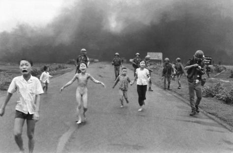 """Una niña completamente desnuda gritando """"¡muy caliente, muy caliente!"""". Presa del pánico  huía  tras su hermano. El fuego carbonizó sus ropas y quemó el 65% de su cuerpo, especialmente la espalda y el brazo izquierdo (1972)."""